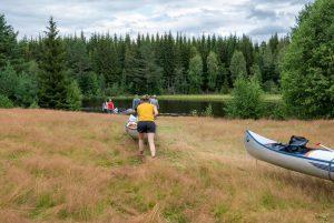 Van de weg het laatste stukje door een veld naar een rivier, hier konden we de kano's zo het water in rijden (Bas Wetter)